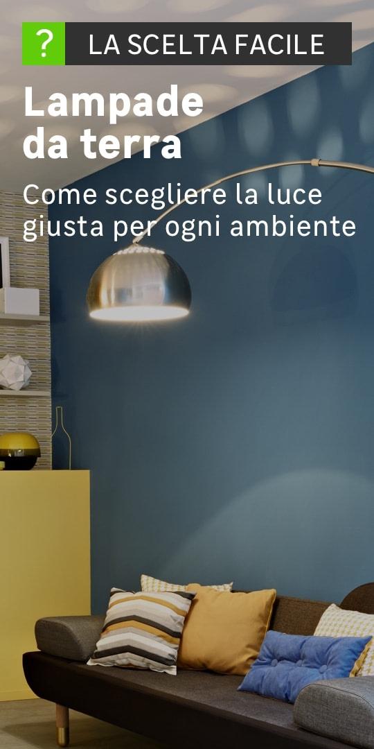 In una stanza arredata c'è una lampada da terra alta e fatta in metallo
